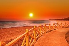 O por do sol na praia no recurso tropical foto de stock