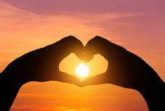 O por do sol na silhueta entrega a fatura da forma do coração Imagens de Stock