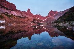 O por do sol nas montanhas aproxima o lago Luz solar refletida em partes superiores da montanha A luz dourada do céu refletiu em  Imagens de Stock Royalty Free