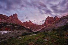 O por do sol nas montanhas aproxima o lago Luz solar refletida em partes superiores da montanha A luz dourada do céu refletiu em  Fotografia de Stock