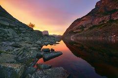 O por do sol nas montanhas aproxima o lago Luz solar refletida em partes superiores da montanha A luz dourada do céu refletiu em  Foto de Stock