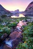 O por do sol nas montanhas aproxima o rio Luz solar refletida em partes superiores da montanha A luz dourada do céu refletiu em u Imagens de Stock
