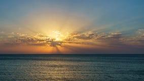 O por do sol no mar nas nuvens com sol irradia Fotografia de Stock