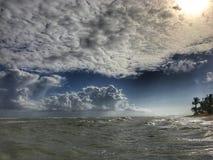 O por do sol do oceano O sol de ajuste destaca algumas nuvens de cúmulo com raios dourados Fotos de Stock Royalty Free