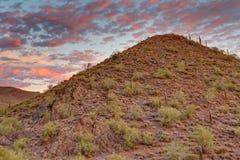 O por do sol pinta o céu sobre a paisagem do deserto Foto de Stock Royalty Free