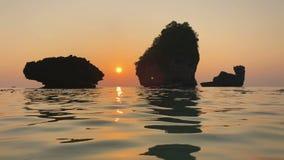 O por do sol romântico em pedras da rocha da costa do Oceano Índico aumenta acima da água, das ondinhas na superfície do mar e da filme