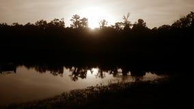 O por do sol sobre a água fotografia de stock