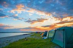 O por do sol vermelho brilhante sobre a praia, lá é um número de barracas Acampamento do turista Imagem de Stock Royalty Free