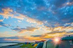 O por do sol vermelho brilhante sobre a praia, lá é um número de barracas Acampamento do turista Imagens de Stock