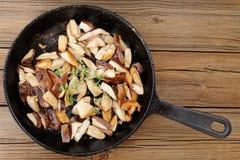 O porcini fritado cresce rapidamente com tomilho fresco no frigideira do ferro fundido sobre Fotos de Stock Royalty Free