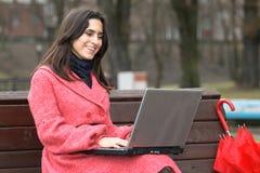 O portátil da menina no parque fotos de stock royalty free