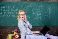 O portátil da posse do professor da mulher senta o fundo do quadro da sala de aula da tabela O conferente da senhora sabe estada  imagens de stock
