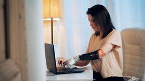O portátil está obtendo operado por uma jovem mulher com um braço biônico filme
