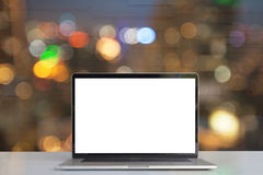O portátil que mostra a tela vazia na mesa vê completamente luzes na cidade o Imagens de Stock Royalty Free