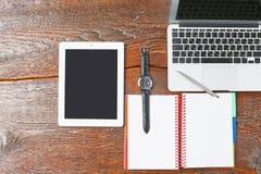 O portátil, a tabuleta e o caderno estão em uma tabela de madeira Foto de Stock