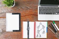 O portátil, a tabuleta e o caderno estão em uma tabela de madeira Fotos de Stock Royalty Free