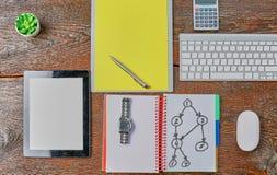 O portátil, a tabuleta e o caderno estão em uma tabela de madeira Imagem de Stock