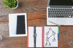 O portátil, a tabuleta e o caderno estão em uma tabela de madeira Fotos de Stock