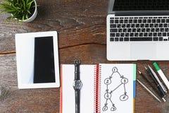 O portátil, a tabuleta e o caderno estão em uma tabela de madeira Imagens de Stock Royalty Free
