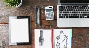 O portátil, a tabuleta e o caderno estão em uma tabela de madeira Foto de Stock Royalty Free