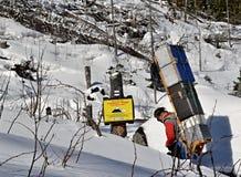 O portador das montanhas com uma carga pesada toma bens a um chalé Imagens de Stock