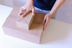 O portador verifica as caixas embaladas, seladas com a fita por todos os lados, volta Fotografia de Stock Royalty Free