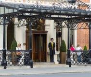 O porteiro no vestido e no chapéu alto tradicionais na entrada ao hotel no verde do ` s de St Stephen, Dublin de Shelbourne fotografia de stock