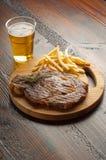 O porterhouse grelhado com francês frita e cerveja Fotografia de Stock