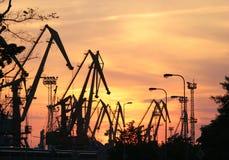 O porto comercial cranes silhuetas no por do sol, fundo vermelho do céu Imagens de Stock Royalty Free