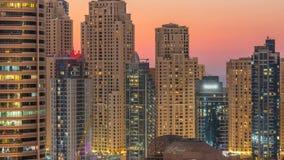 O porto de Dubai e dos twers de JBR dia do panorama às luzes do timelapse da noite gerenciem sobre filme