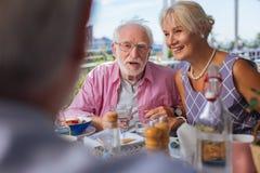 O positivo envelheceu os povos que têm uma reunião no restaurante imagem de stock
