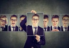 O positivo mascarou o homem novo nos vidros que expressam emoções diferentes fotos de stock