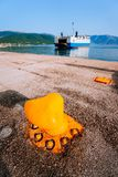 O poste de amarração alaranjado da amarração e o ferryboat grande com passageiros e carros chegam ilha grega bonita Férias de ver fotos de stock royalty free