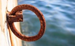 O poste de amarração oxidado espera no cais por um barco a ser amarrado Borre o mar para o fundo, close up, detalhes, bandeira Imagem de Stock Royalty Free