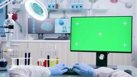 O POV disparou das mãos do cientista que datilografam no computador com tela verde filme