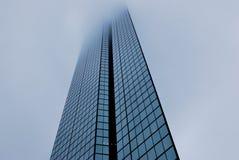 O prédio de escritórios moderno do vidro olha como uma lâmina de faca na névoa Foto de Stock