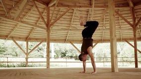 O practician masculino da ioga executa o suporte nos braços no salão do treinamento com a abóbada de madeira filme