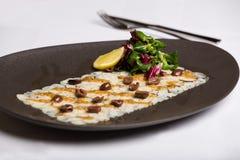 O prato de peixes serviu com porcas, rúcula e limão Fotografia de Stock Royalty Free
