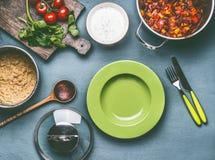 O prato de vegetariano saudável com quinoa cozinhado, molho dos feijões dos tomates, serviu com a placa vazia no fundo da mesa de Foto de Stock Royalty Free