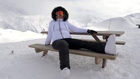 O prazer do esquiador da mulher relaxa nas montanhas que sentam-se no banco video estoque