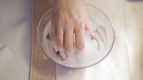 O prego hidratando do procedimento, mão coloca no banho com água Close-up Salão de beleza do tratamento de mãos o manicuro faz filme