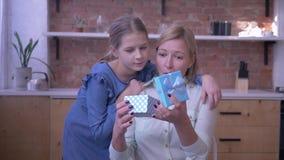 O presente à mamã, menina dá a mãe atual para o feriado e abraça-a delicadamente em casa e mum surpreendido