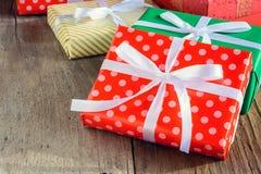 O presente da caixa de presente e decora em uma tabela de madeira Foto de Stock