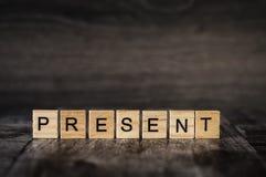 O presente da palavra é feito de cubos de madeira brilhantes com lette preto Imagens de Stock Royalty Free