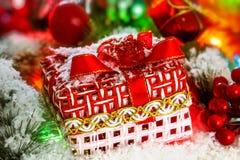 O presente de Natal vermelho está na neve contra um fundo de uma bola do Natal e de um ouropel brilhante Luzes de incandescência  Fotos de Stock