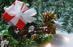 O presente do Natal aninhou-se nas decorações com folha de prova da neve imagens de stock royalty free
