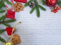 O presente do Natal, cones do pinho, pão-de-espécie, abeto ramifica com doces, pirulito em um fundo do branco do tijolo fla fotos de stock royalty free