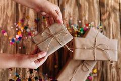 O presente envolvido para um partido toma as mãos das mulheres fora da tabela fotos de stock royalty free
