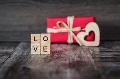 O presente na caixa vermelha, o coração de madeira e a palavra amam, alinhado com Imagens de Stock