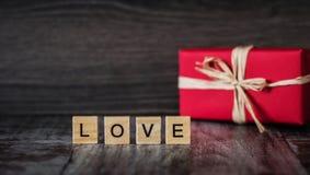 O presente na caixa vermelha e a palavra amam, alinhado com blocos de madeira, na Dinamarca Fotos de Stock Royalty Free